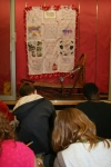 A traveling Iditarod quilt being observed by sixth graders